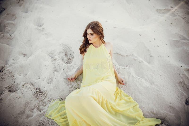 Bella ragazza di boho che posa sulla spiaggia sabbiosa alla luce di tramonto vicino alla l fotografie stock