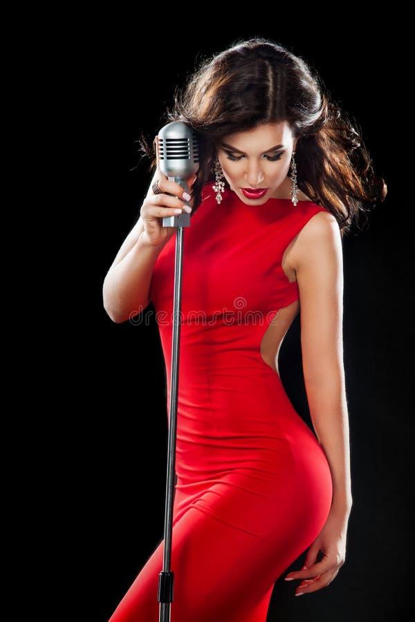 Bella ragazza di canto Donna di bellezza in vestito rosso con il microfono fotografia stock