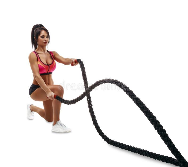 Bella ragazza di forma fisica che fa addestramento facendo uso della corda del crossfit fotografia stock