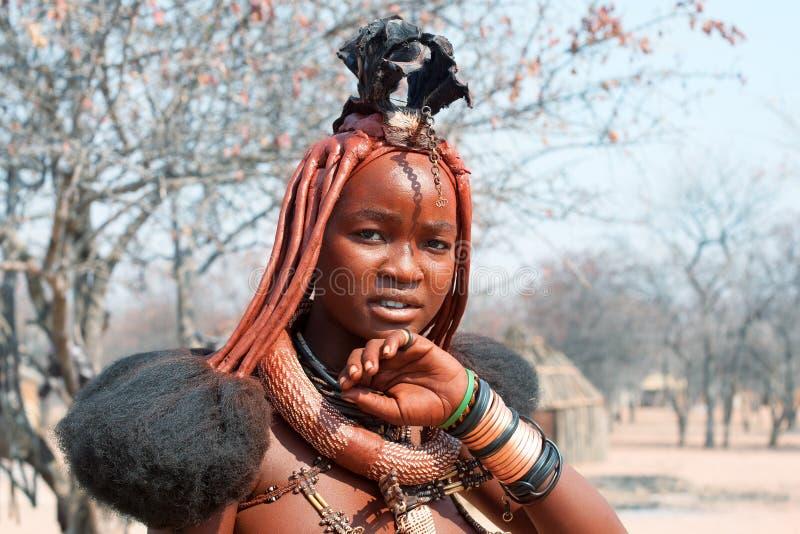 Bella ragazza di himba con l'acconciatura, gli anelli, la collana ed i braccialetti nazionali sul fondo tradizionale del villaggi fotografia stock libera da diritti