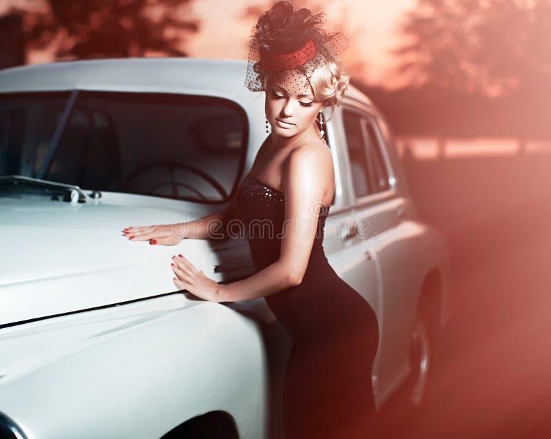 Bella ragazza di modo nel retro stile che si siede in vecchia automobile fotografie stock libere da diritti