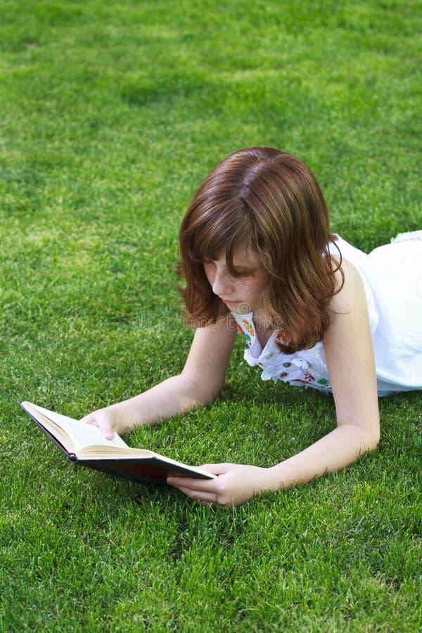 Bella ragazza di Teen.Young che legge un libro all'aperto fotografia stock libera da diritti