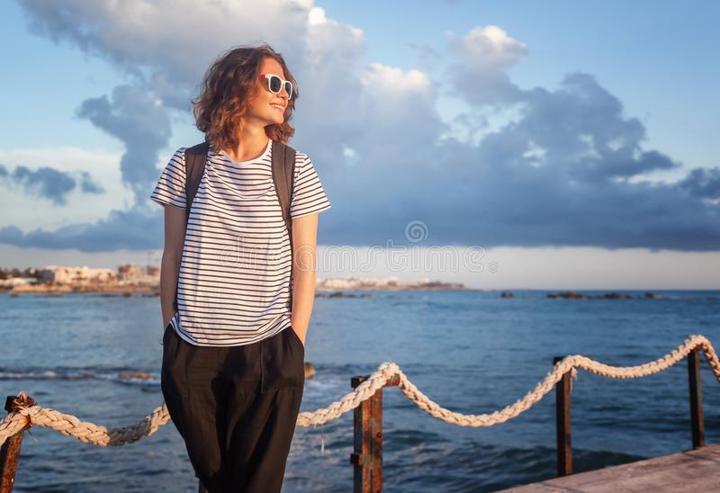 Bella ragazza di viaggio della giovane donna su un fondo del pilastro del mare in a fotografie stock