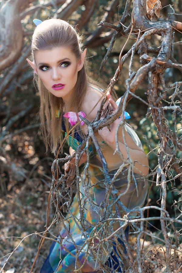 Bella ragazza dolce delicata nel carattere di fiaba nel ruolo dell'elfo di legno che cammina attraverso la foresta con le farfall immagini stock libere da diritti