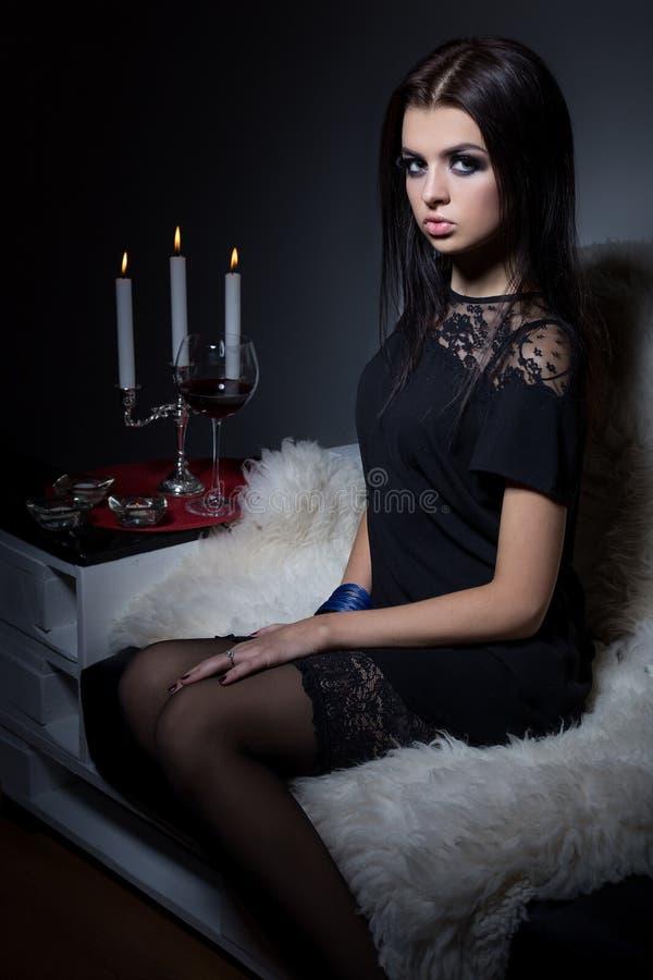 Bella ragazza dolce sexy con trucco luminoso delle labbra piene che si siede sul sofà con un bicchiere di vino in un vestito da s fotografia stock