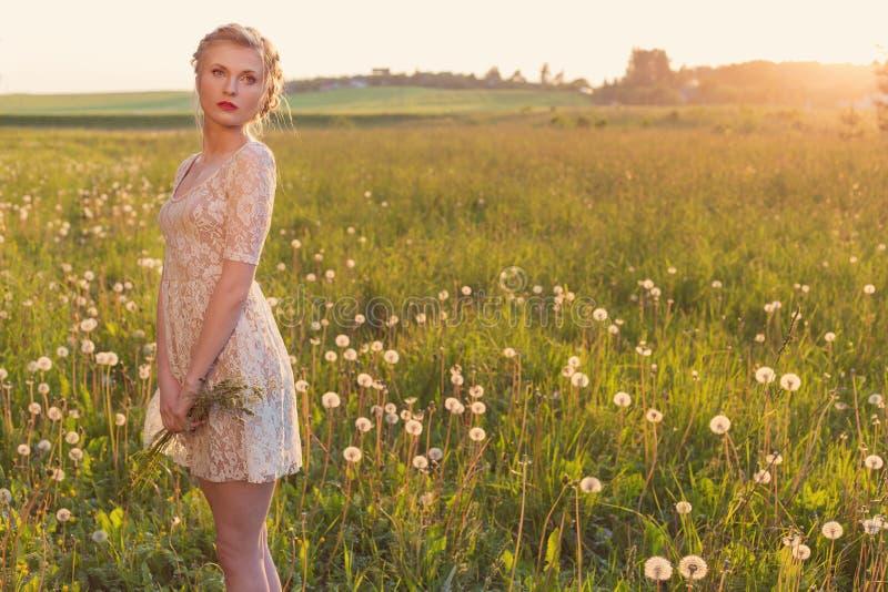 Bella ragazza dolce tenera in un vestito bianco dal pizzo con una falce sulla sua testa che sta a piedi nudi in un campo dei dent fotografia stock libera da diritti
