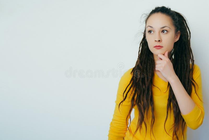 Bella ragazza dubbiosa premurosa con i dreadlocks ed in un maglione luminoso giallo con la mano incerta della tenuta del fronte s fotografia stock libera da diritti