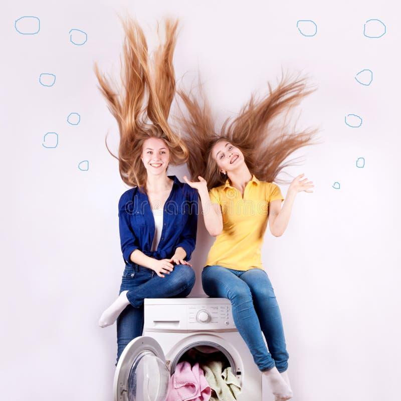 Bella ragazza due con capelli scorrenti e una lavatrice fotografie stock