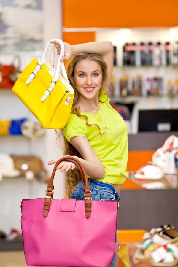 Bella ragazza e borse di cuoio nel deposito fotografia stock