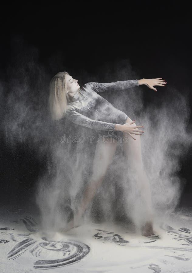 Bella ragazza esile che indossa una tuta relativa alla ginnastica nera coperta di nuvole dei balli bianchi volanti della polvere  fotografia stock