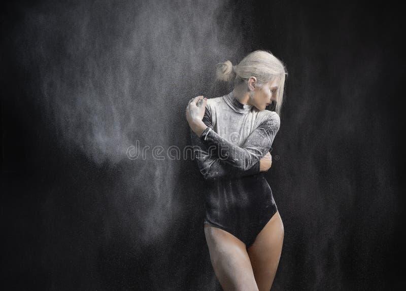 Bella ragazza esile che indossa una tuta relativa alla ginnastica nera coperta di nuvole dei balli bianchi volanti della polvere  immagine stock