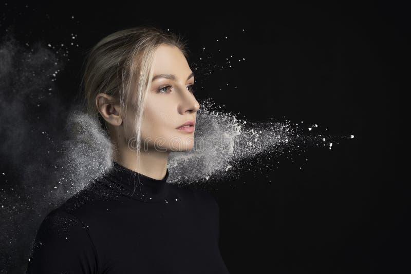 Bella ragazza esile che indossa una tuta relativa alla ginnastica nera coperta di nuvole delle pose bianche volanti della polvere fotografie stock libere da diritti