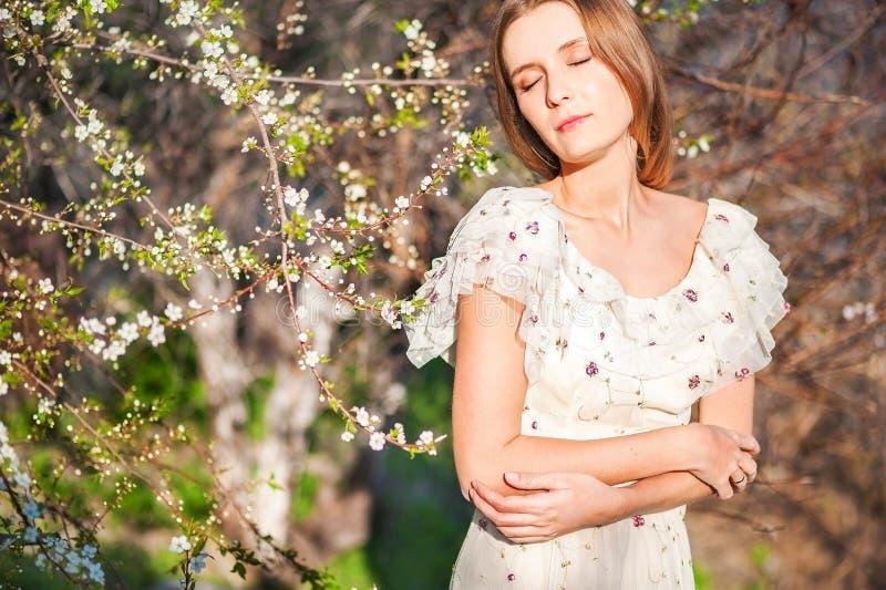 Bella ragazza esile con capelli biondi in un vestito leggero lungo contro il contesto della natura, alberi di fioritura, a casa,  fotografie stock