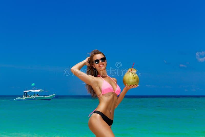 Bella ragazza felice in bikini con la noce di cocco su un tropicale fotografie stock libere da diritti