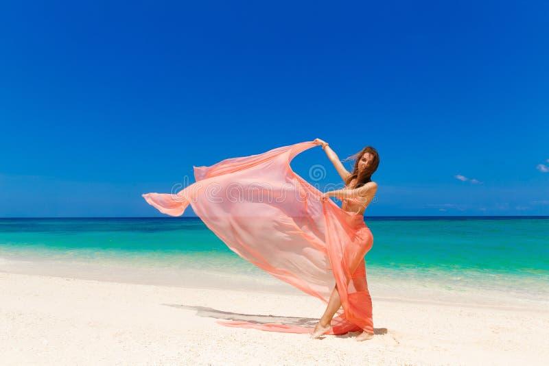 Bella ragazza felice in bikini rosa con l'ondeggiamento nella vittoria fotografia stock
