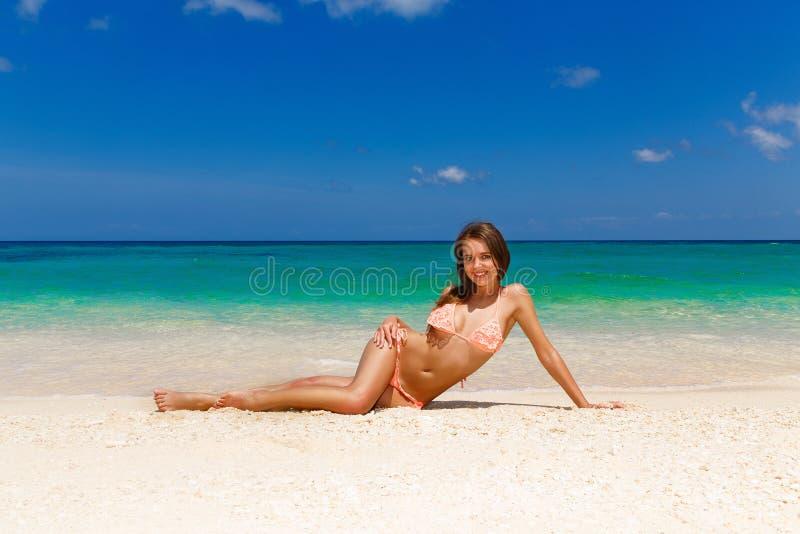 Bella ragazza felice in bikini su una spiaggia tropicale S blu fotografia stock