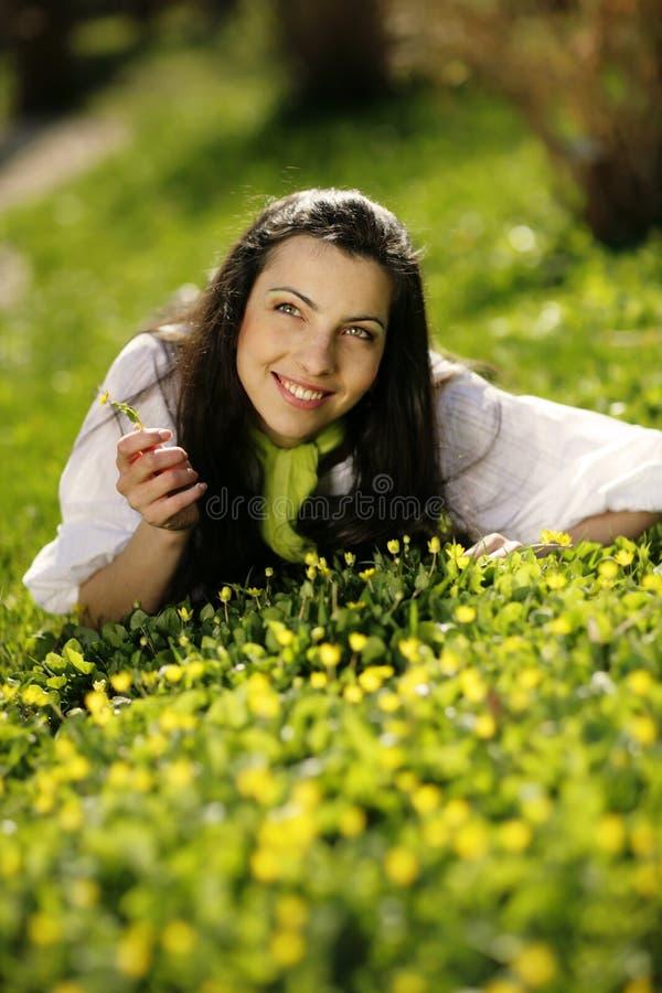 Bella ragazza felice che si trova nell'erba immagini stock libere da diritti