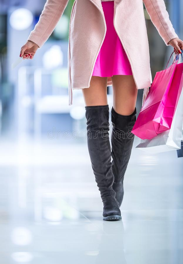 Bella ragazza felice con la carta di credito e sacchetti della spesa nello shopp fotografia stock libera da diritti