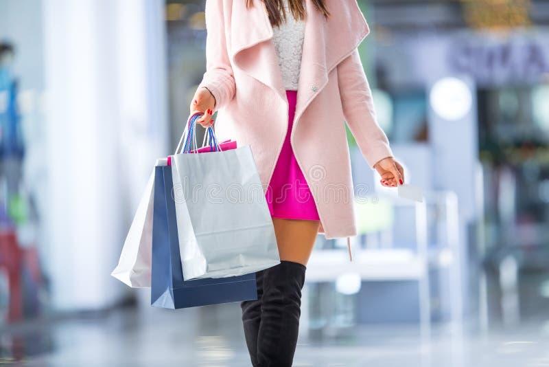 Bella ragazza felice con la carta di credito e sacchetti della spesa nello shopp fotografia stock