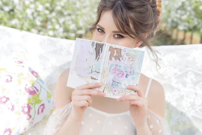 Bella ragazza felice delicata dolce in un vestito beige dal boudoir con i fiori in una tenuta del canestro, foto che elabora nell immagine stock libera da diritti