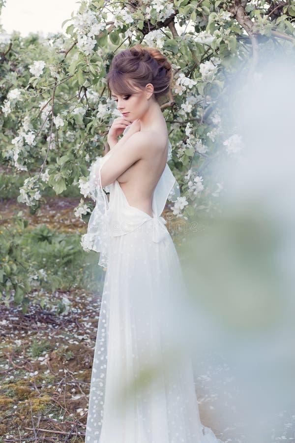 Bella ragazza felice delicata dolce in un vestito beige dal boudoir con i fiori in una tenuta del canestro, foto che elabora nell fotografia stock libera da diritti