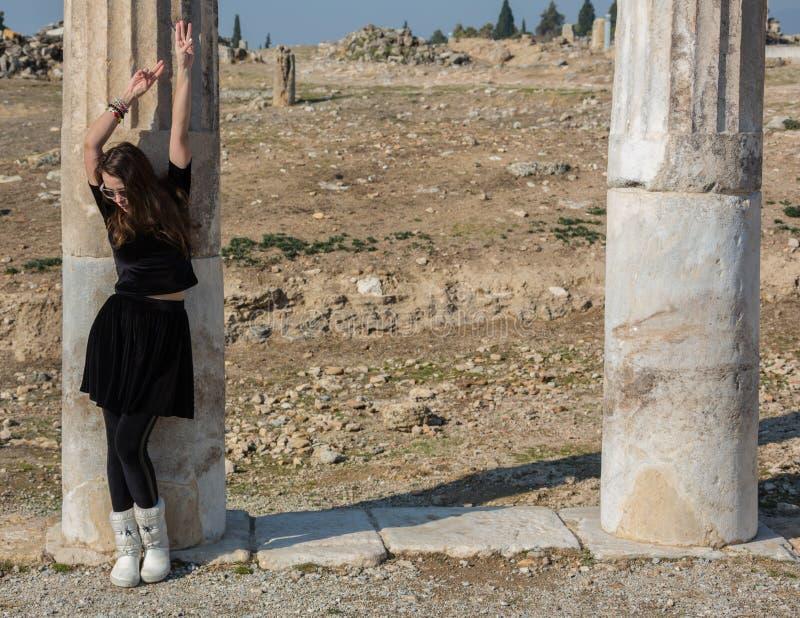 Bella ragazza greca che tiene una nave antica nel teatro antico dell'isola di Thassos, Grecia fotografia stock libera da diritti