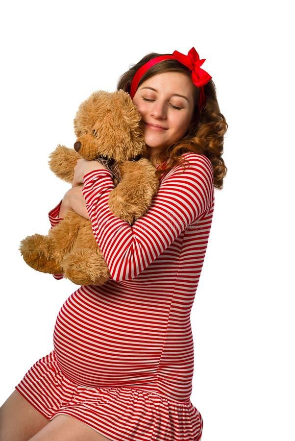 Bella ragazza incinta che abbraccia un giocattolo immagine stock