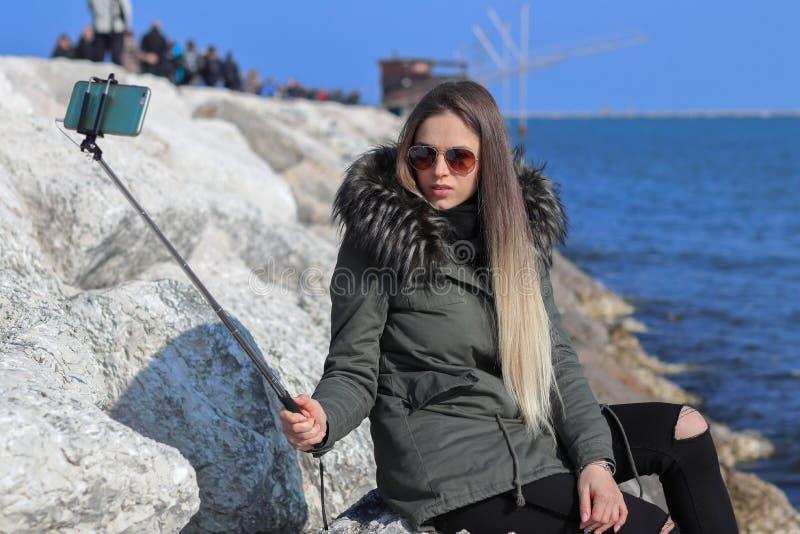 Bella ragazza La ragazza d'avanguardia fa un selfie sulla spiaggia con il mare nei precedenti fotografia stock