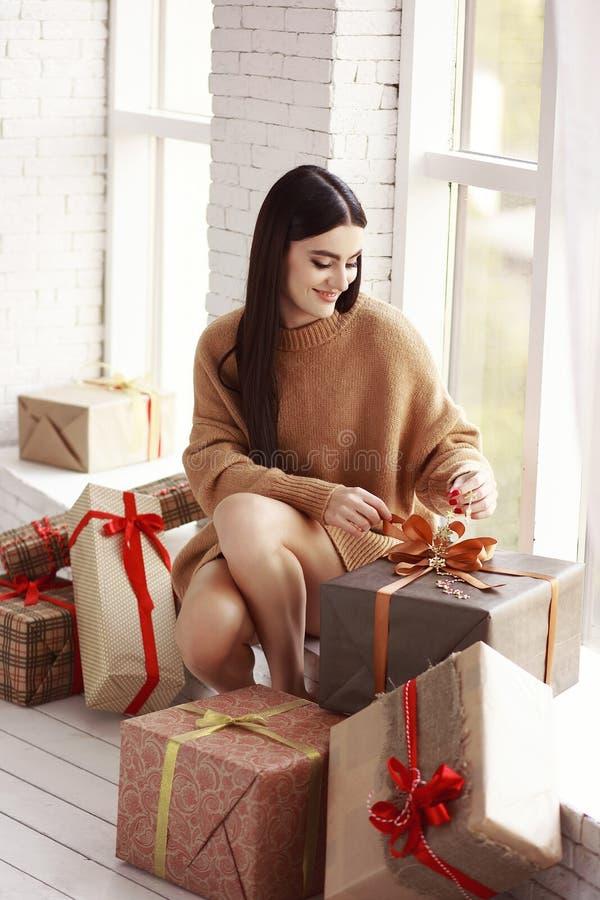 Bella ragazza in maglione che si siede sulla finestra Regali, nuovo anno immagine stock