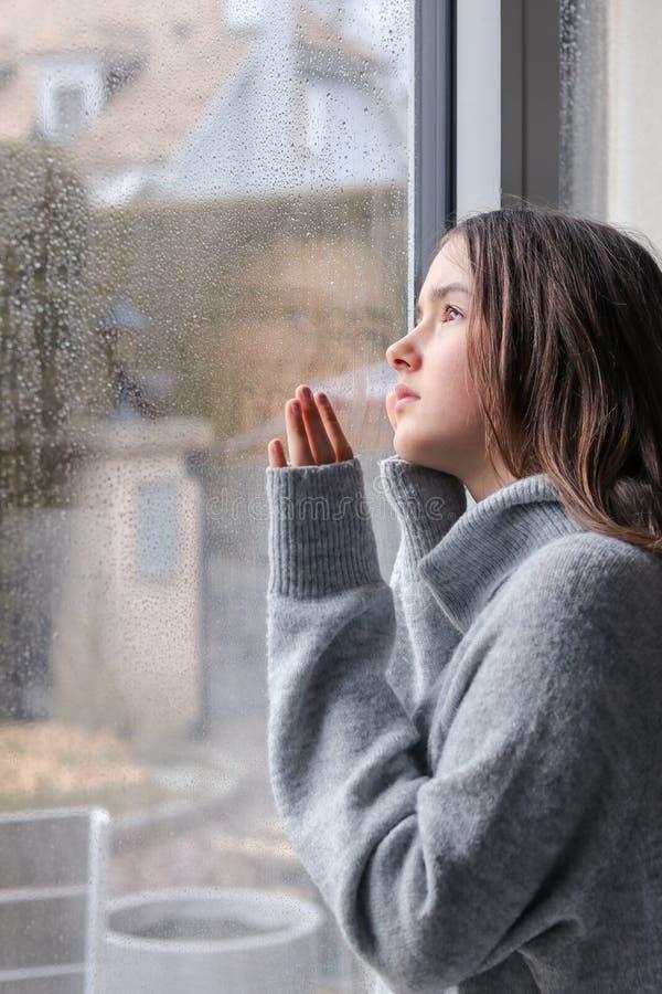 Bella ragazza malinconica dell'adolescente in maglione grigio caldo che esamina esterno attraverso le gocce di pioggia sulla fine fotografia stock