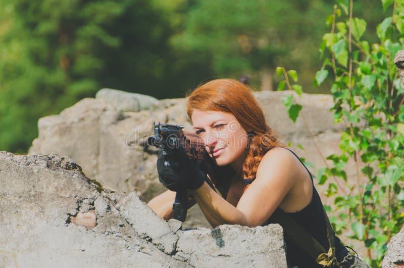 Bella ragazza militare che tende un'arma basata sulla copertura concreta fotografia stock libera da diritti
