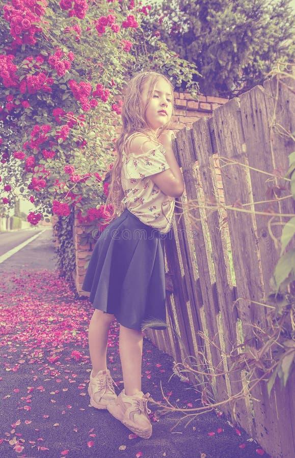 Bella ragazza in mini gonna che pende contro un recinto di legno accanto ad un bello fiore fotografia stock