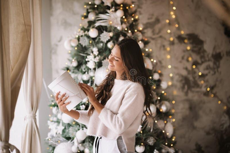 Bella ragazza mora vestita nei supporti bianchi dei pantaloni e del maglione accanto alla finestra sui precedenti del nuovo immagini stock