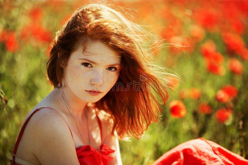 Bella ragazza nel campo del papavero fotografia stock