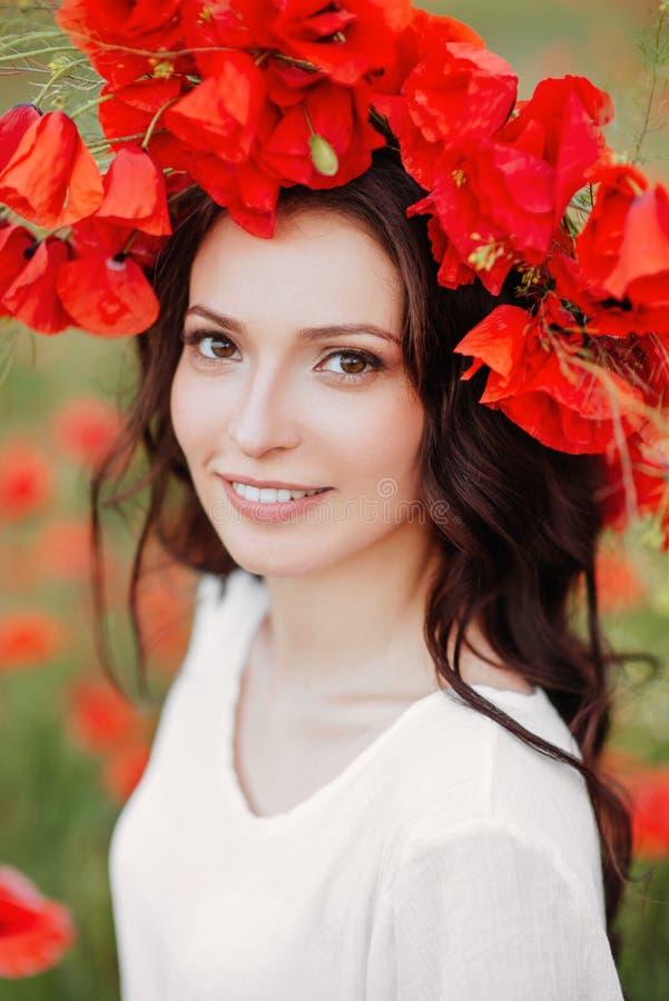 Bella ragazza nel campo rosso del papavero fotografia stock libera da diritti