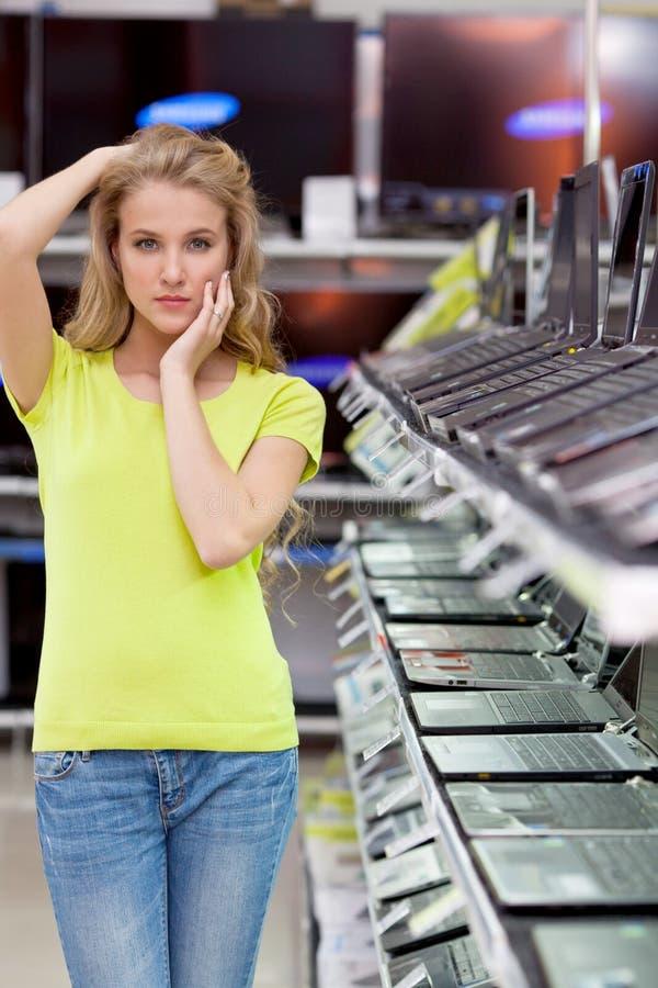 Bella ragazza nel dipartimento dei computer portatili nel deposito di elettronica immagini stock libere da diritti