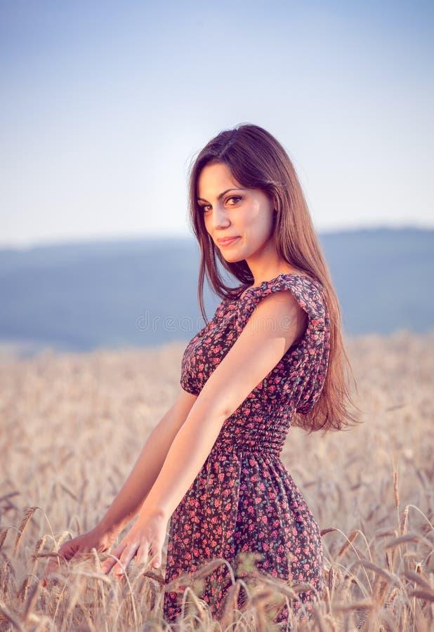 Bella ragazza nel giacimento di grano al tramonto fotografia stock libera da diritti