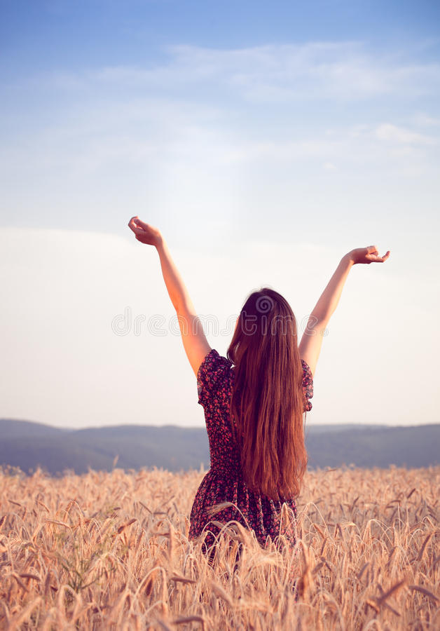 Bella ragazza nel giacimento di grano al tramonto fotografia stock