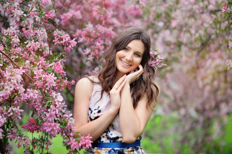 Bella ragazza nel giardino di primavera fra gli alberi di fioritura immagine stock