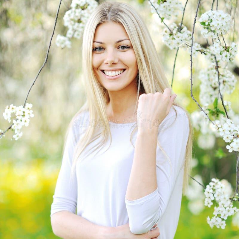 Bella ragazza nel giardino fra gli alberi di fioritura fotografia stock libera da diritti