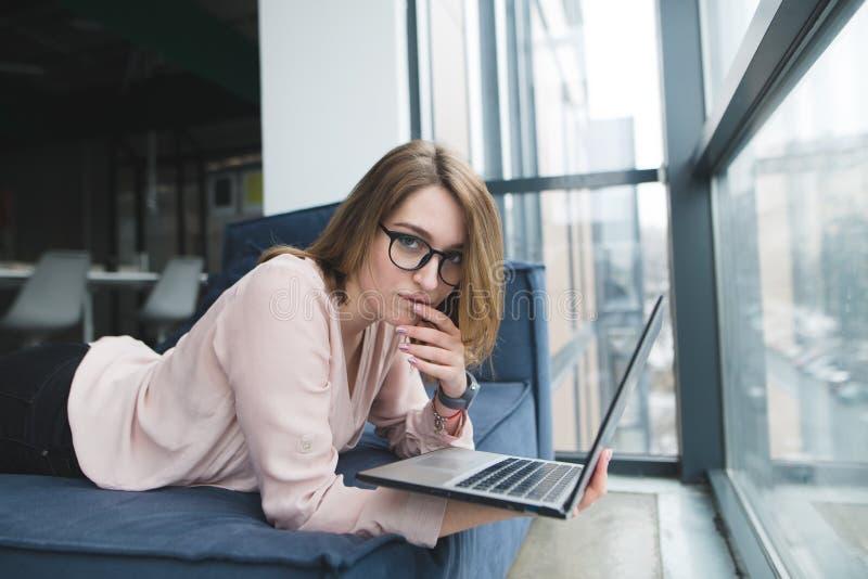 Bella ragazza nell'ufficio su un sofà con un computer portatile in sue mani immagini stock