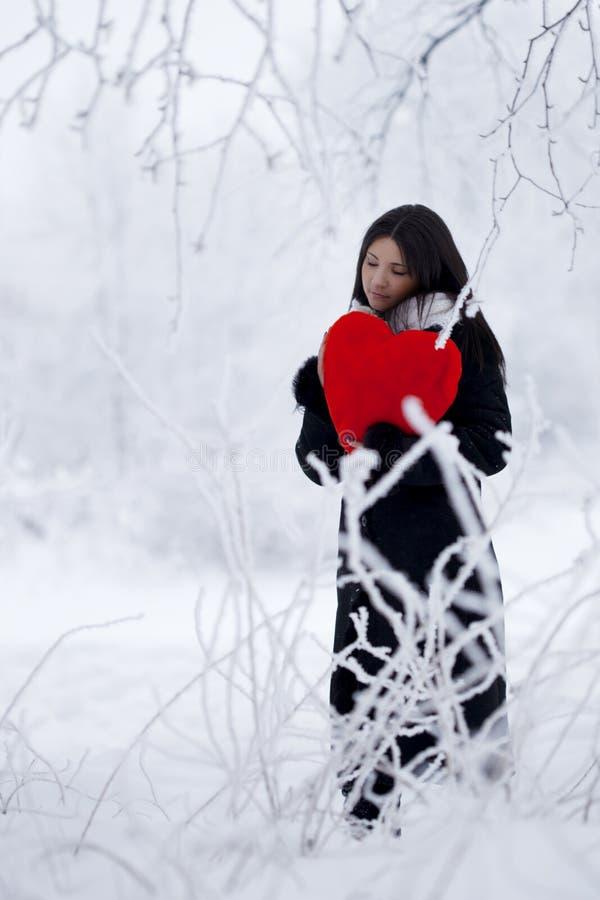 Bella ragazza nella foresta di inverno nel colore rosso fotografia stock libera da diritti