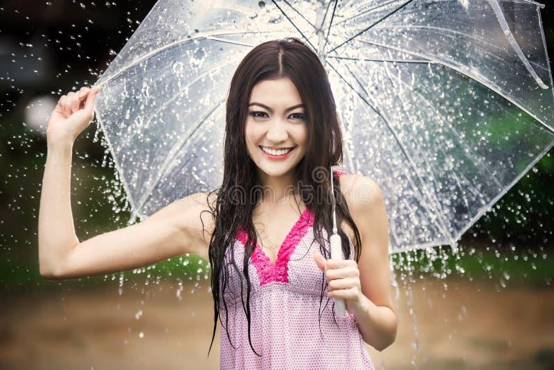 Bella ragazza nella pioggia con l'ombrello trasparente fotografia stock
