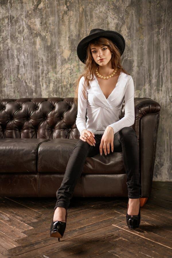 Bella ragazza nella seduta black hat sul sofà, donna alla moda fotografia stock