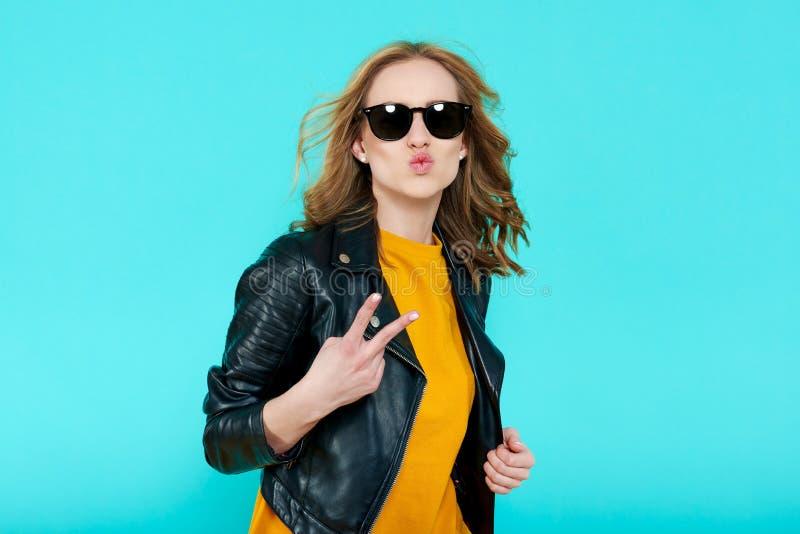 Bella ragazza pazza della roccia in bomber ed occhiali da sole neri Il punk non è morto Giovane donna che fa gesto di mano del se fotografia stock