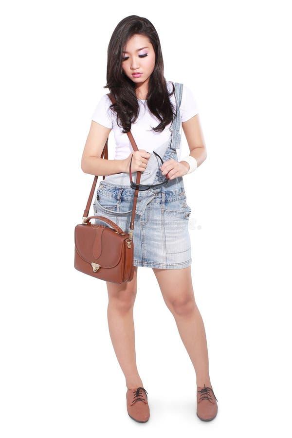 Bella ragazza pensierosa con una borsa ed i vetri di trasporto fotografie stock libere da diritti