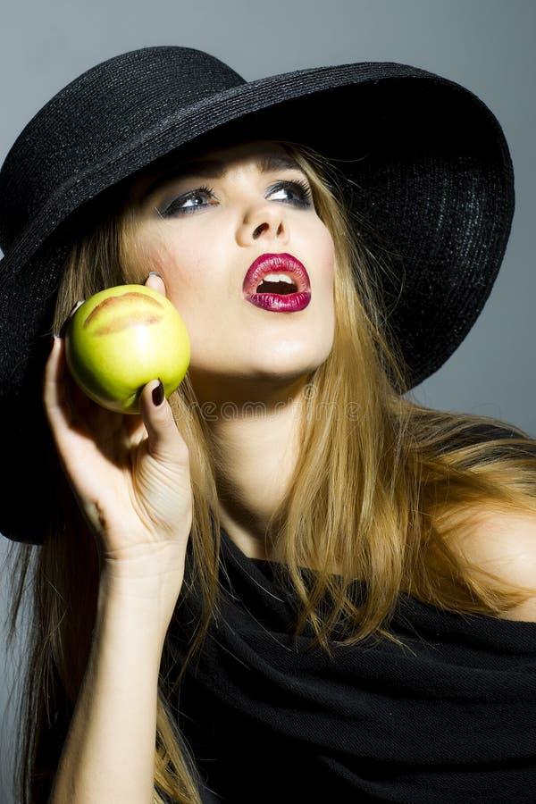 Bella ragazza in retro black hat con la mela fotografia stock libera da diritti
