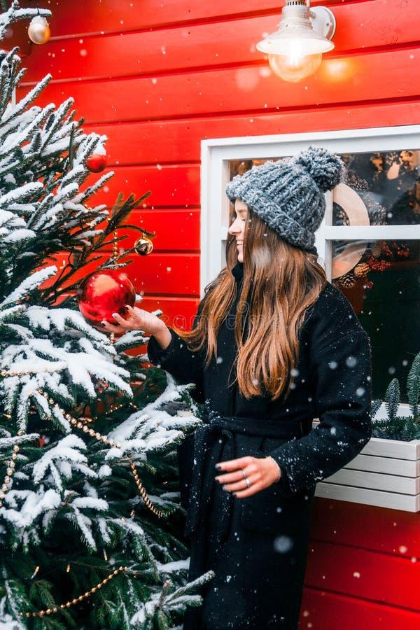 Bella ragazza russa in un giorno della nuvola in vestiti di inverno con la palla di natale in mani divertendosi nel quadrato di T immagini stock