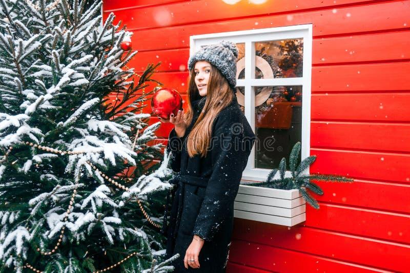 Bella ragazza russa in un giorno della nuvola in vestiti di inverno con la palla di natale in mani divertendosi nel quadrato di T fotografie stock libere da diritti