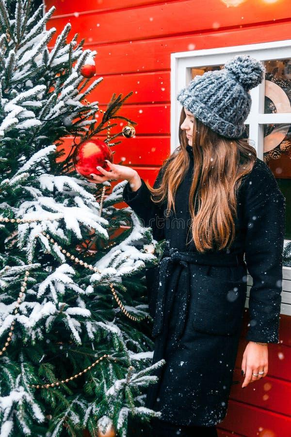 Bella ragazza russa in un giorno della nuvola in vestiti di inverno con la palla di natale in mani divertendosi nel quadrato di T immagine stock